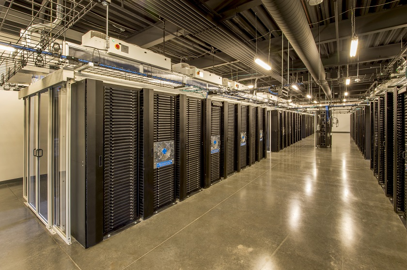 Large server room with enclosed, climate controlled server racks.